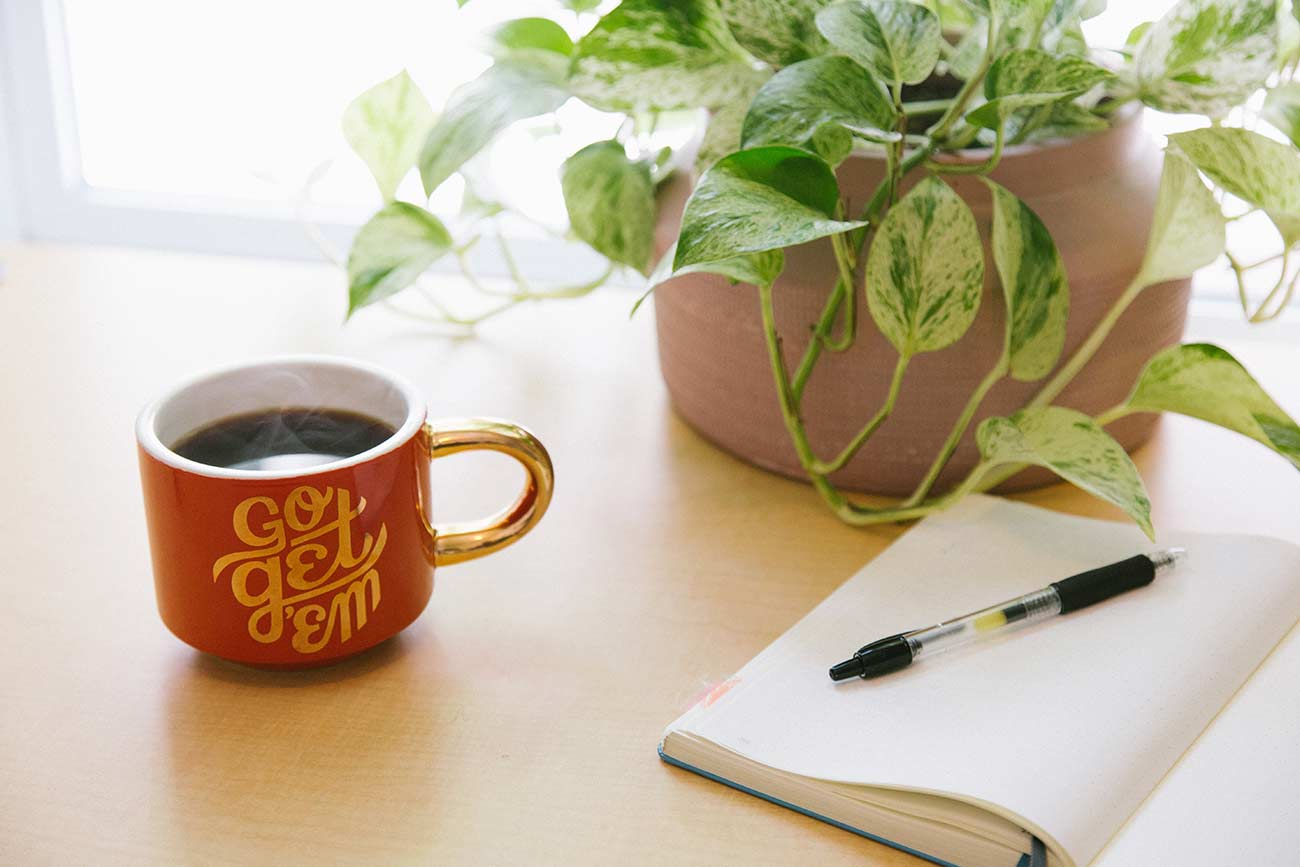 Coffee cup and copywriting notepad on bright desk